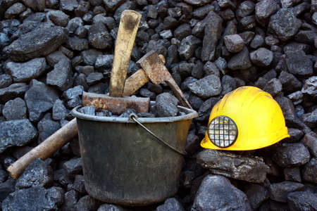 Pile of coal from mine deposit of black mineral stones and tools of miners Stock Photo