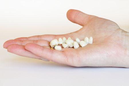 dentures: Porcelain crown and bridge (dentistry) on a hand