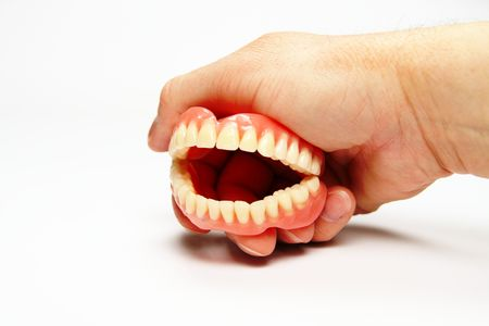 lower teeth: The total denture upper and lower held in the hand Stock Photo
