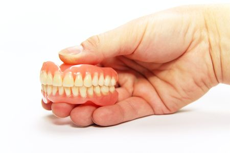 The total denture upper and lower held in the hand photo