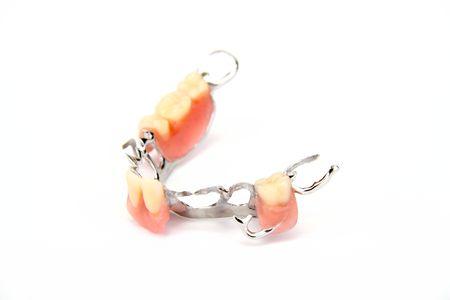 dentadura postiza: Dientes artificiales sobre fondo blanco.