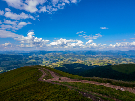dirt road on the ridge of a tall mountain covered with green dense grass rising to a blue sky with clouds Stock Photo