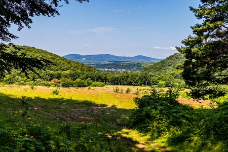 The glade between the hills is lit by the bright sun in the summer. Convenient place for camping