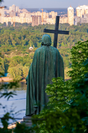 bronze monument to Volodymyr the great with a cross on the river Dnipro contemplates the city of Kiev