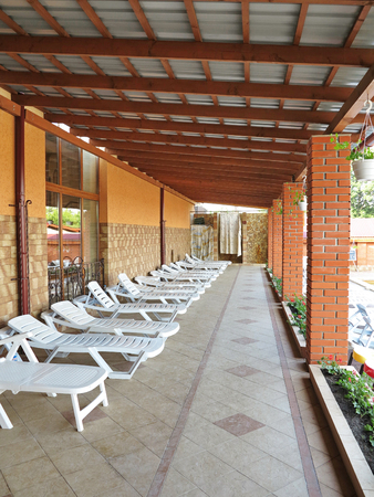 Terrace with a tiled floor covered with slate sheets and standing white sun beds for relaxation.