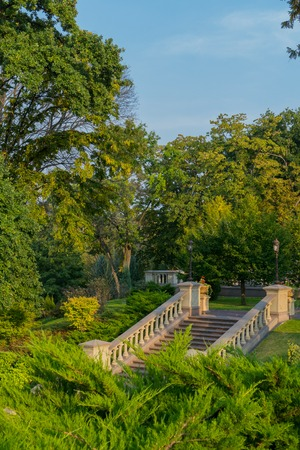 A staircase in a park with low handrails with lanterns for lighting in the evening is among trees and green lawns. 免版税图像