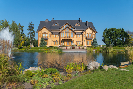 A terrace near the lake with a fountain in front of a luxurious wooden house. Mezhyhirya Ukraine