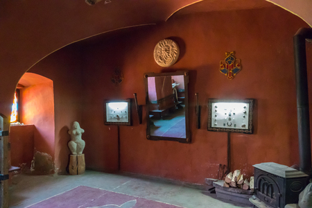 A room with beautiful exhibits. Mirror, statue, family coat of arms and other things