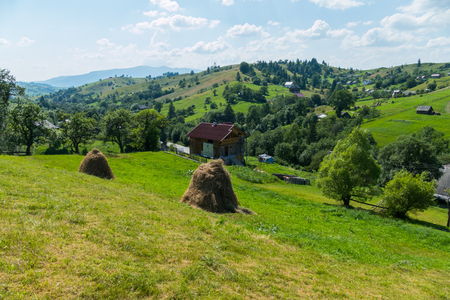 Transcarpathian village with a haylage built in a log hut near the scattered hills of houses Stock Photo