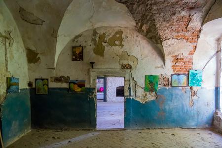 壁に絵画や子供の絵が描かれた荒廃した建物の遺跡のアーチ