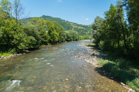 A mountain shallow river with clear water and a bottom filled with stones flowing among Stockfoto