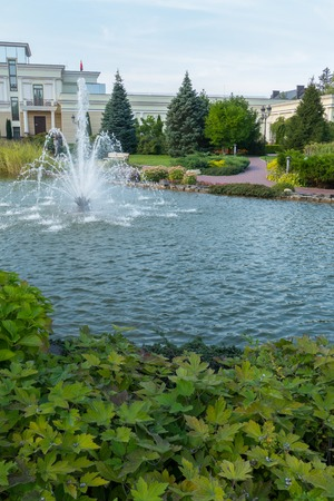 beautiful fountain in a pond surrounded by green on the background of a light mansion and a blue cloudless sky