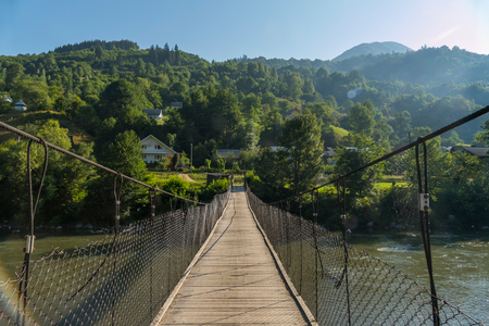 pedestrian bridge across a mountain river leading to rural houses drowning in the green of trees