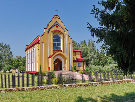 Yellow-red Catholic church with a green lawn, fenced with a beautiful forged fence