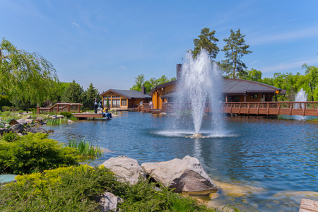 A tall beautiful beating fountain in the middle of a blue lake against a background of wooden buildings with decorative bridges