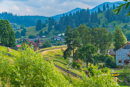 The railway makes a turn on the background of the village and the picturesque nature around it. Banco de Imagens