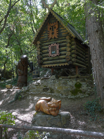 Sculptures of an orange cat and Baba Yaga on the background of a hut on chicken legs Stock fotó