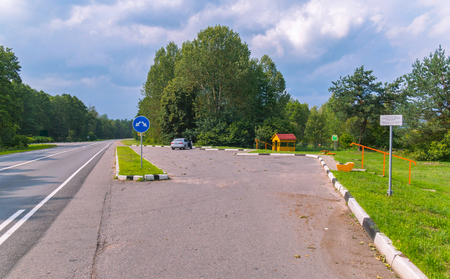 The car stopped at the side of the road against the backdrop of a beautiful landscape with green trees Foto de archivo