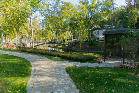A promenade park avenue with a beautiful green lawn on the background of a decorative bridge across the pond