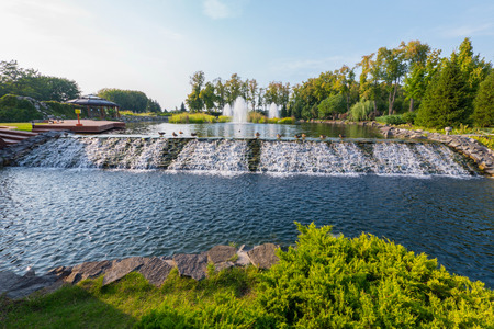 An artificial cascading waterfall flows from a lake in the park near a wooden gazebo with a terrace. Novi Petrivtsi, Ukraine