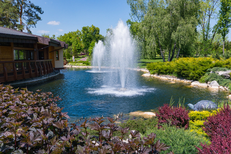 View of an ornamental lake with two beating fountains and beautiful flower beds on the sides