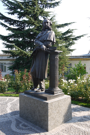 A monument with a standing man leaning on a column with large sideburns and drawing brushes. Located next to the flowerbed with flowers and a high lush spruce. Editorial