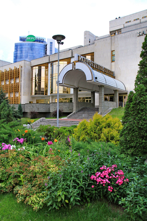 Beautiful green flowerbed with ornamental flowers and small coniferous trees on the background of the entrance to the conference center