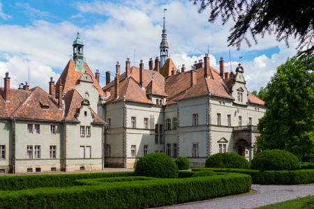 An ancient beautiful castle with a tiled roof and a decorative park green area