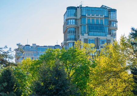 high-rise building with many windows and glass balconies on the background of the tops of trees with yellow and green foliage Editorial
