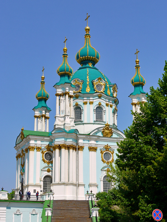 Beautiful massive church with green gilt domes on a clear blue sky background Editorial