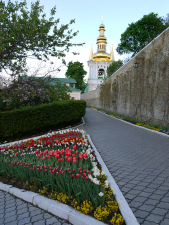 Triangular flowerbed with multi-colored tulips against a beautiful church church in the distance