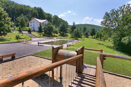 Wooden railing of the dais with a beautiful view of the pool in the park with the resting people with a green lawn nearby and standing in the distance home. Reklamní fotografie