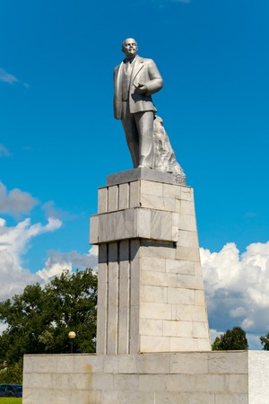 The monument of the historical person V.I. Lenin standing on a high pedestal against the blue sky. One of the most common monuments on the teritory of the former USSR.