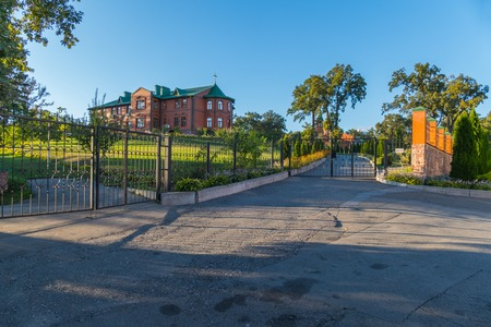 An asphalted playground in front of the gate leading to a beautiful two-story brick house standing on a hill with a beautiful garden in the yard. Stock Photo