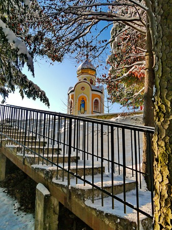 Snow-covered steps leading to a small church, against a backdrop of tall trees