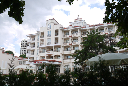 Beautiful views of the beautiful hotel with luxurious architecture and many balconies from under the trees with green foliage growing next to it.
