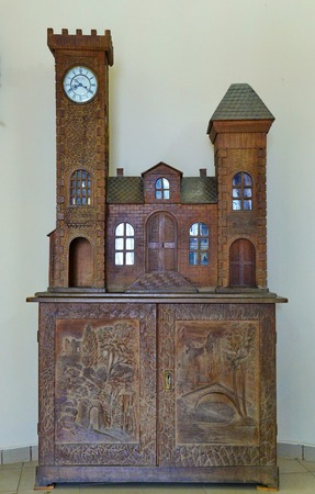 Carved wooden hand-made cabinet made of wood. With beautiful turrets with glasses and clocks. And the pictures on the doors are carved directly on them. Editorial