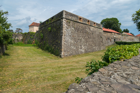 High stone fortification wall with windows against a green lawn background Editorial