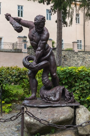 Sculpture depicting a man with a truncheon of a conquering serpent near his feet. Standing on the stones behind the fence with a chain near the green bushes in front of the house.