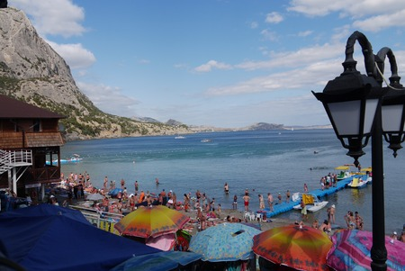 A beach full of tourists and colorful umbrellas by the sea coast in the background of a high rocky mountain Editorial