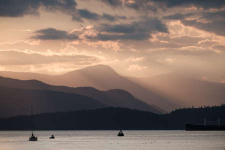 山と海に沈む夕日 写真素材