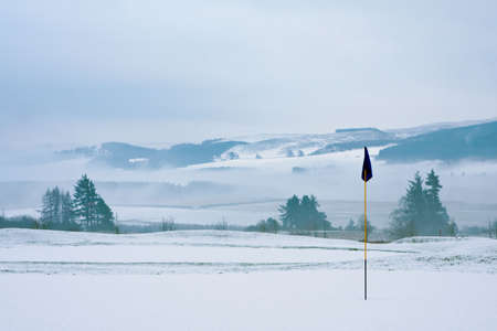 wintry landscape: A golf course in Scotland on a snowy winter morning in December. View from a green with a blue flag, with trees, mist and mountains in the background.