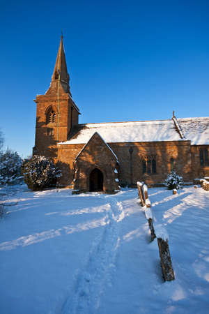 A traditional English village churchyard covered with snow on a sunny winter afternoon, with blue sky in the background.