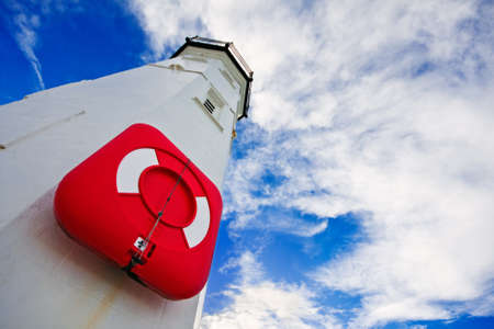 White lighthouse with a red life preserver against a cloudy blue sky on a bright winter morning. Photo taken in Anstruther, Scotland. Standard-Bild