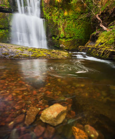Swirling foam in a pool below a waterfall in the Brecon Beacons, Wales, surrounded by the lush greens of spring. Long exposure image.
