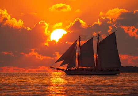 A boat sailing in front of a beautiful sunset in Key West, Florida.