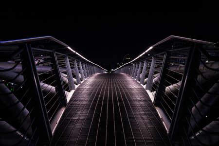 Small pedestrian bridge at night in False Creek, Vancouver. Imagens