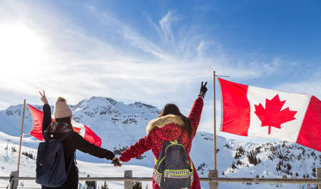 Two girls holding hands in front of a Canadian flag in Whistler.