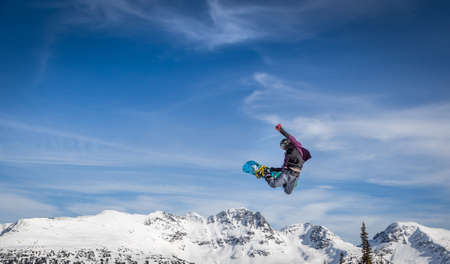 Snowboarder in mid-air grabbing the back of his board. Stock Photo