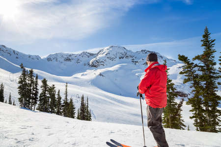 Skier standing in front of Whistler Mountain peak.